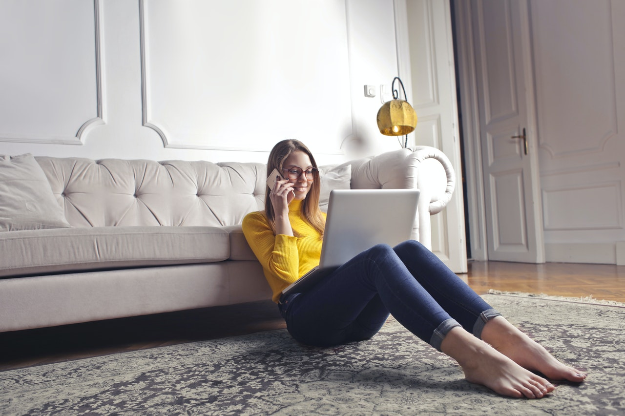 A girl sitting on the floor next to a sofa