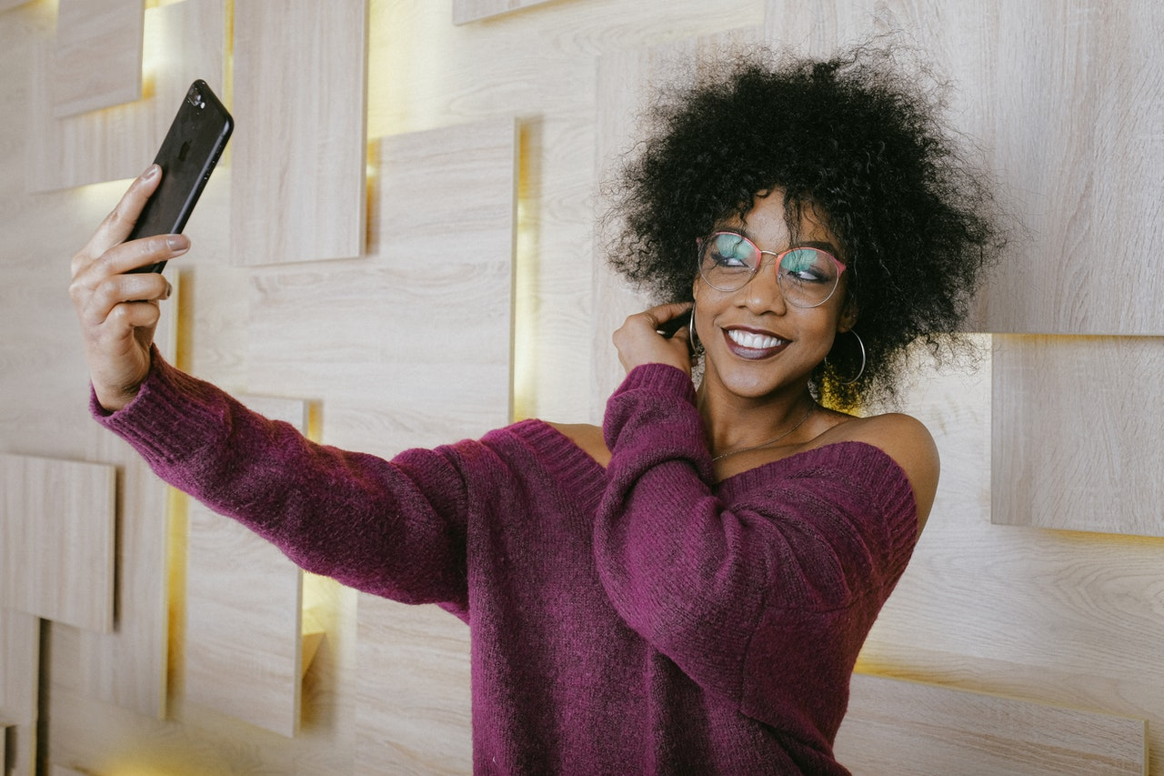 A girl taking a selfie against a white wall