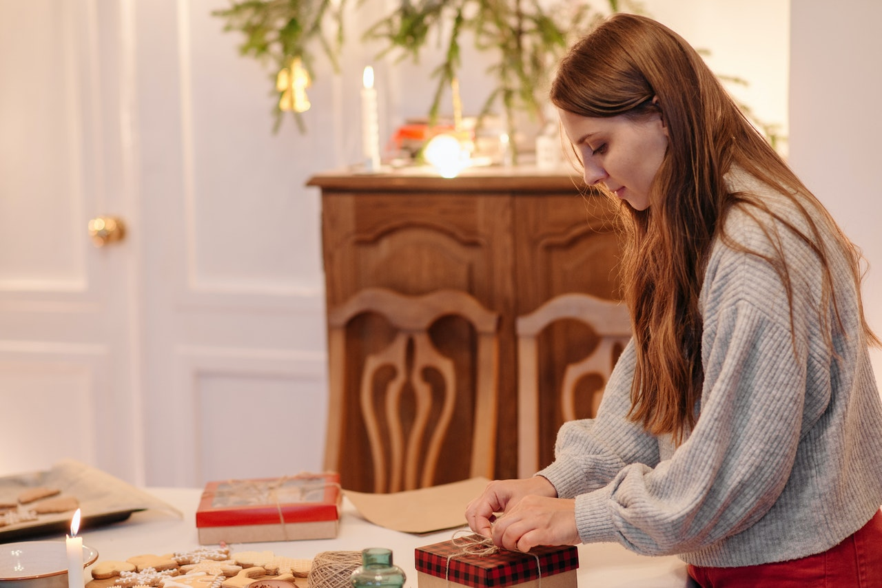 A girl wrapping up a gift indoors