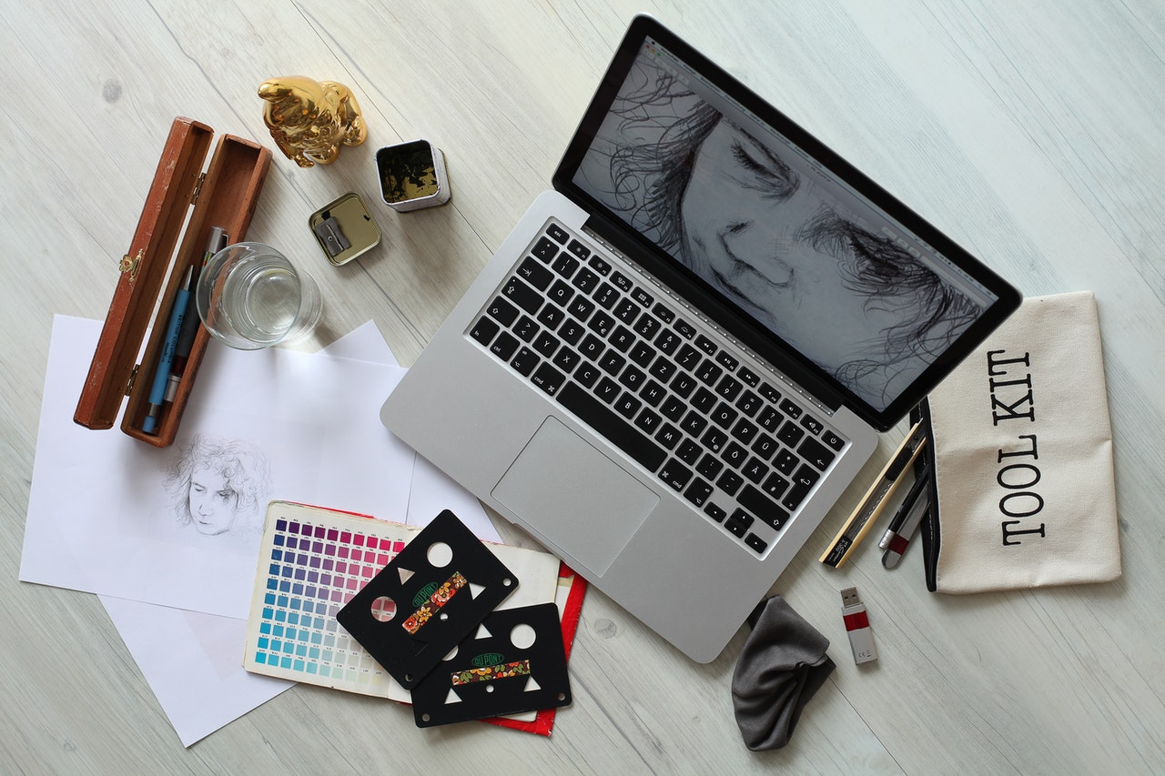A laptop on a desk with graphic design work open on the screen