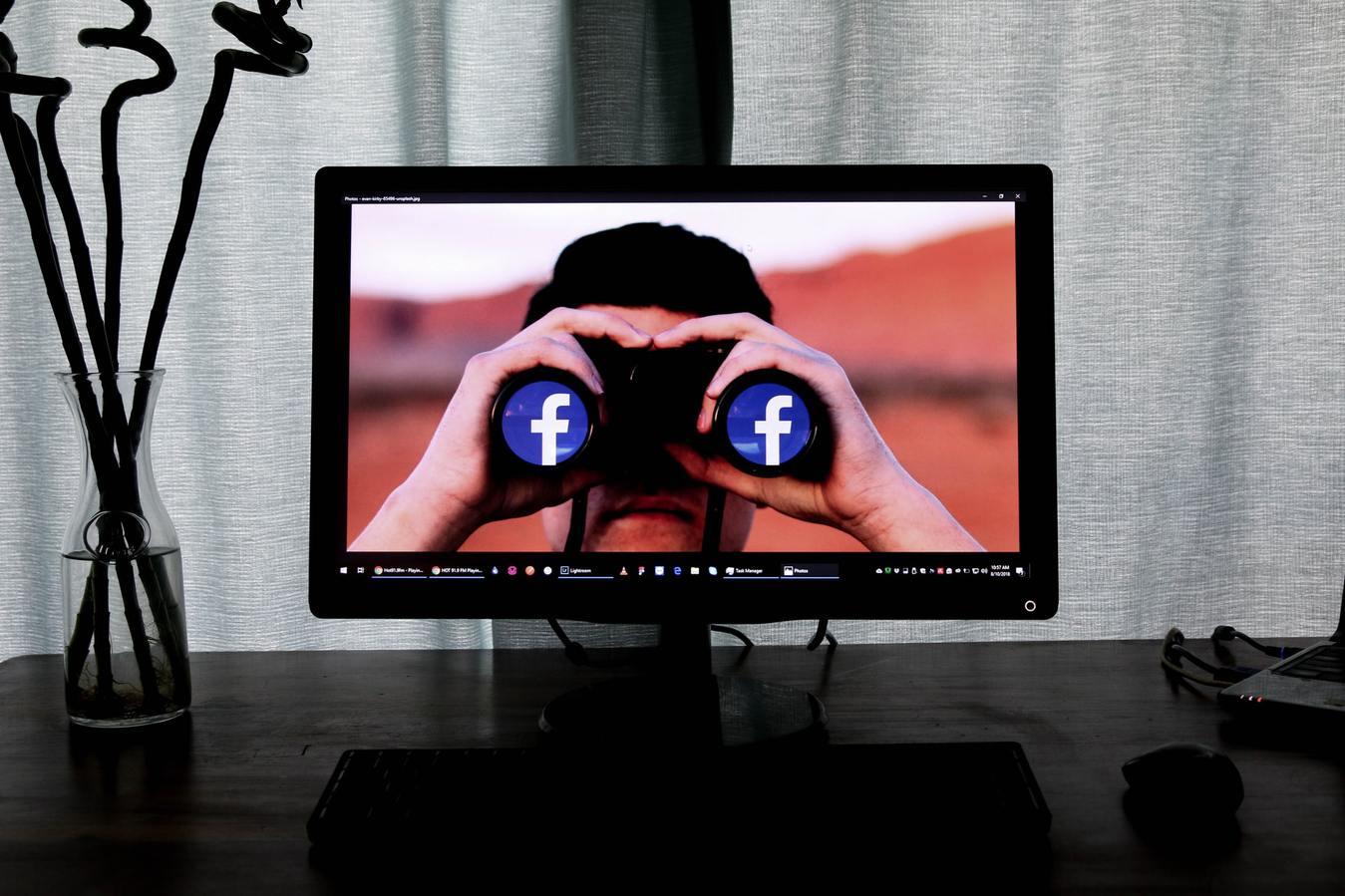 monitor de computador exibindo homem usando binóculos com o símbolo do facebook sobre as lentes