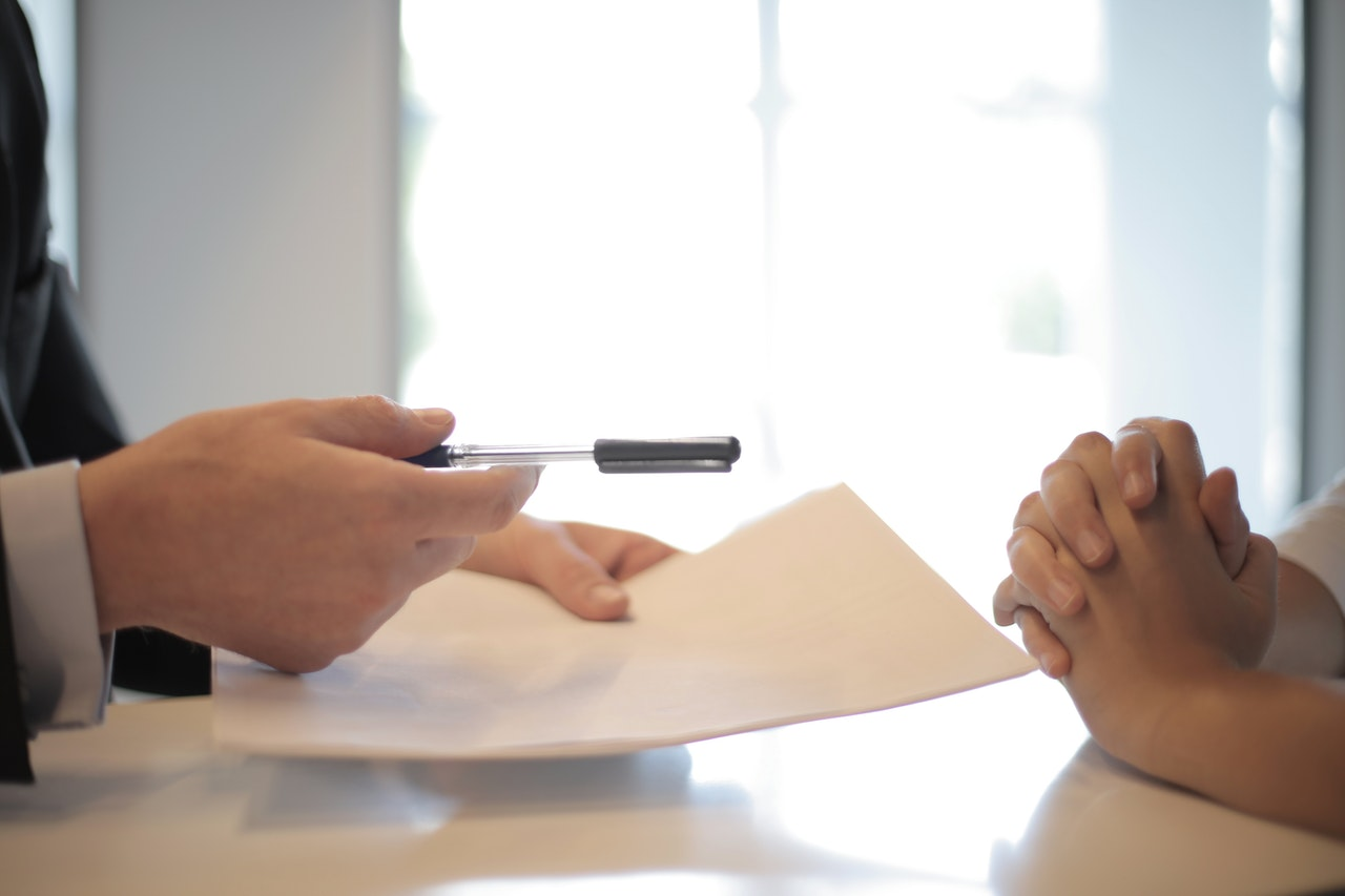 A person handing another person a pen while holding papers