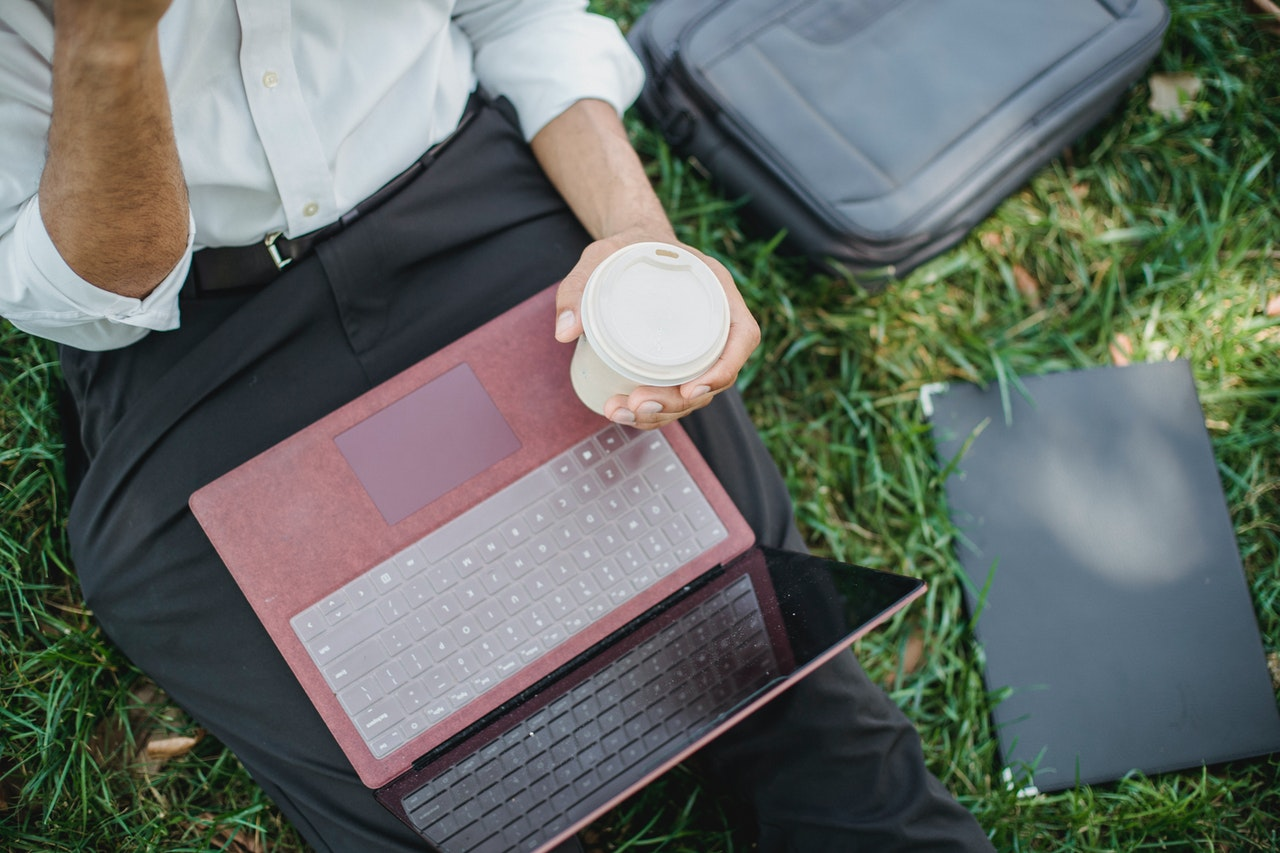 Person outside with a takeaway coffee cup and their laptop in their lap