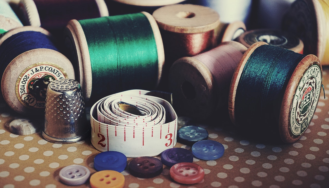 Thread, measuring tape, and other craft things on a table