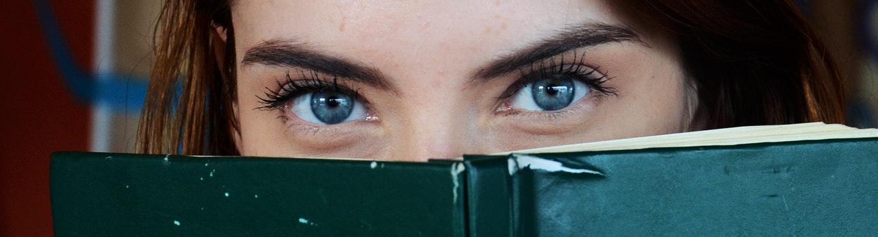 Woman peering behind a book with big eyes