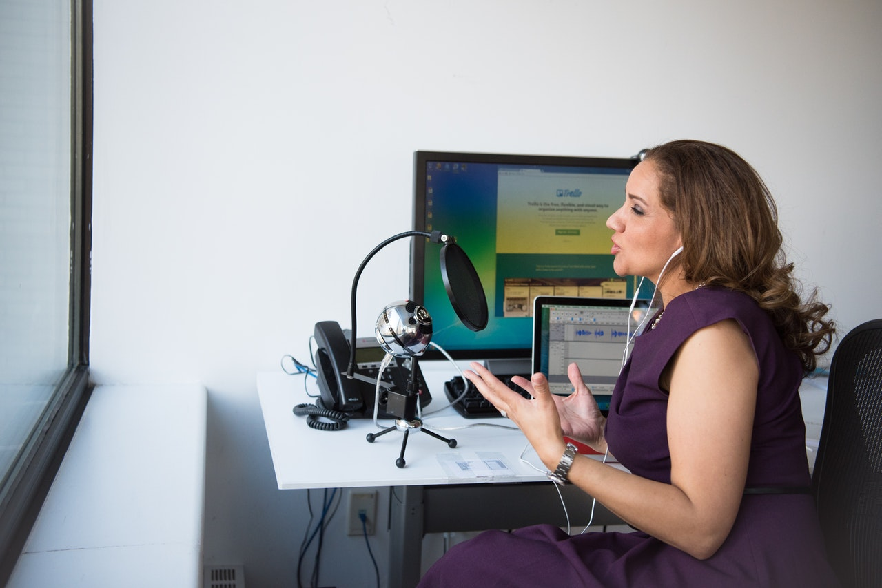 A woman recording a podcast inside