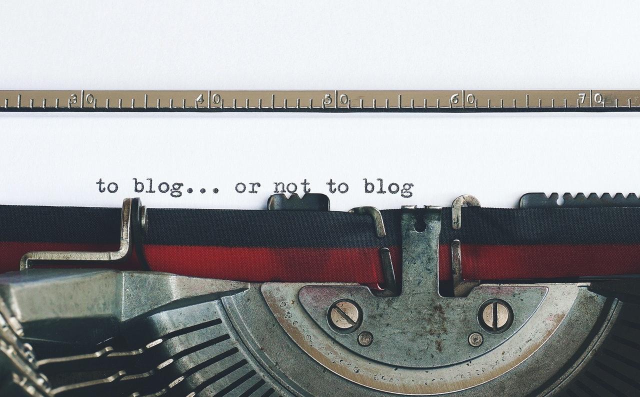 """Vecchia macchina da scrivere con un foglio con scritto """"to blog... or not to blog"""""""