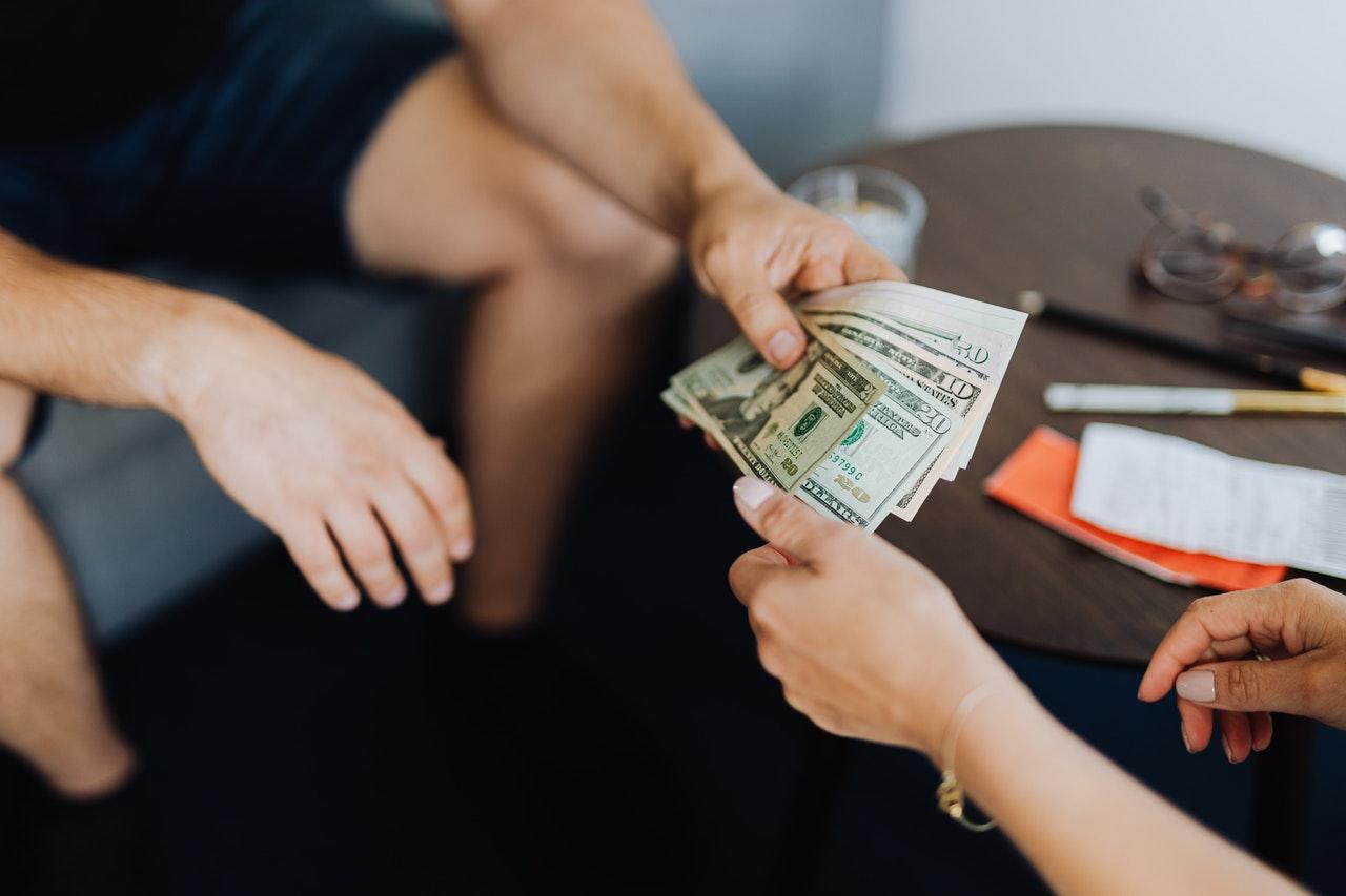 People handing each other money omsode