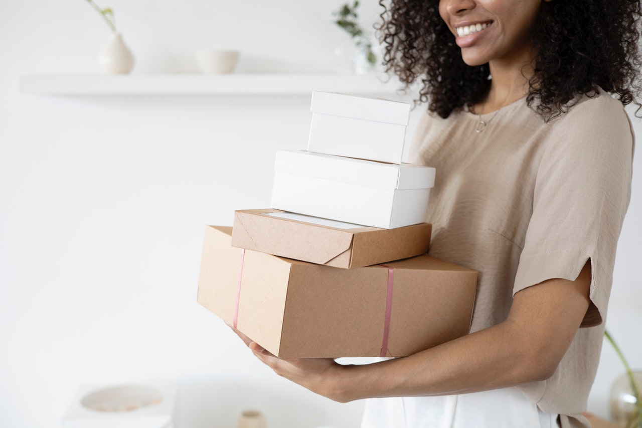 A woman carrying parcel boxes inside against a white background